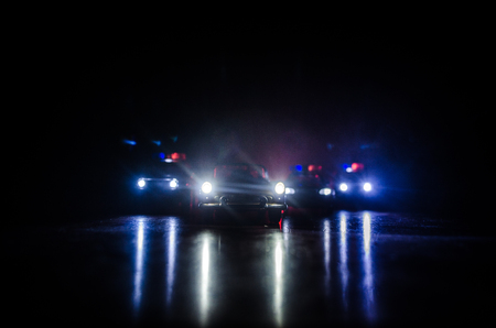 Police car chasing a car at night with fog background.
