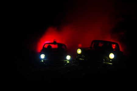Silhouette of police car chasing a car at night with fog background. 911 Emergency response police car speeding to scene of crime. Selective focus Stock Photo