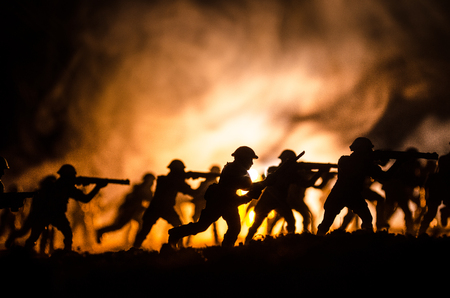 Military silhouettes of soldiers against the backdrop of dark foggy sky Battle scene with explosion and burning clouds behind fighing soldiers. Reklamní fotografie - 90253822