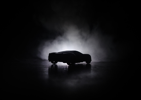 The car in the shadows with glowing lights in low light, or silhouette of sport car dark background. Selective focus Banco de Imagens