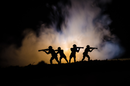 Military silhouettes of soldiers against the backdrop of dark foggy sky Battle scene with explosion and burning clouds behind fighing soldiers.