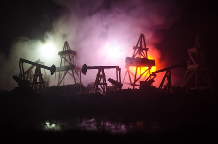 Oil pump oil rig energy industrial machine for petroleum, Group oil rigs and brightly lit industrial site at night. Toned.Background for design. Selective focus