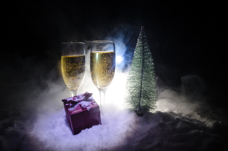 New Years Eve celebration background with pair of flutes and bottle of champagne with christmas tree on snow on dark background. Selective focus