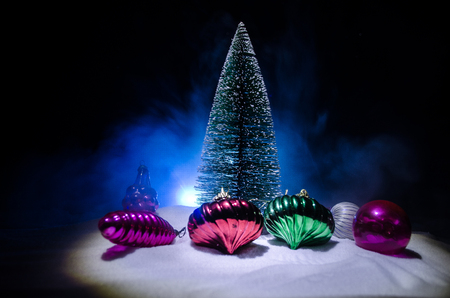 Christmas toys at decorative fir-tree in snow. Making a Christmas tree on table. Empty space. Useful as greeting card Stock Photo