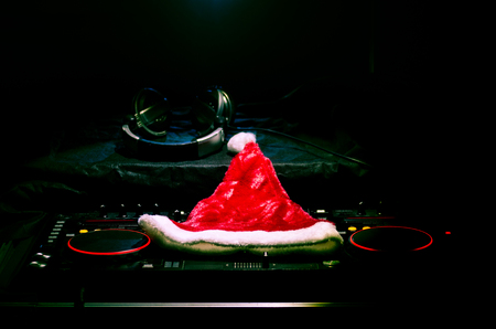 Dj mixer with headphones on dark nightclub background with Christmas tree New Year Eve. Close up view of New Year elements or symbols (Santa Clause, Snowman, Dog 2018, gift box) on a Dj table. Foto de archivo
