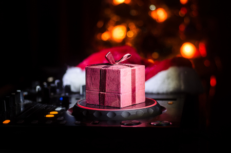 Dj mixer with headphones on dark nightclub background with Christmas tree New Year Eve. Close up view of New Year elements or symbols (Santa Clause, Snowman, Dog 2018, gift box) on a Dj table. Stockfoto