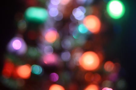 Christmas pine tree defocused. Colorful garland lights are sparkling on the background. Red, blue, and yellow electric lights turning on and off.