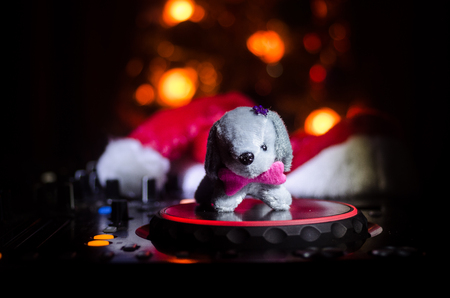 Dj mixer with headphones on dark nightclub background with Christmas tree New Year Eve. Close up view of New Year elements or symbols (Santa Clause, Snowman, Dog 2018, gift box) on a Dj table. Reklamní fotografie