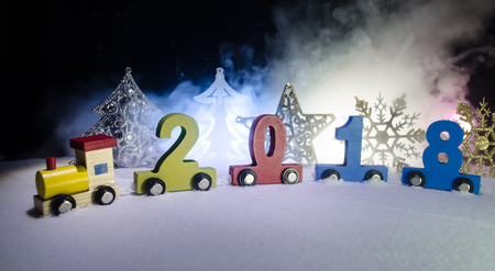 2018 happy new year,wooden toy train carrying numbers of 2018 year on snow. Toy train with 2018. Copy space. Christmas decoration. Selective focus. Dark background Stock Photo