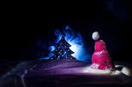 Christmas holiday New Year background with Santa Clause hat and blurred Christmas tree on snowy background.