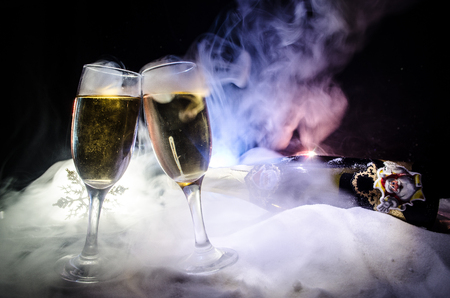 New Year Eve celebration background with pair of flutes and bottle of champagne with Christmas attributes (or elements) on snowy dark toned foggy background.