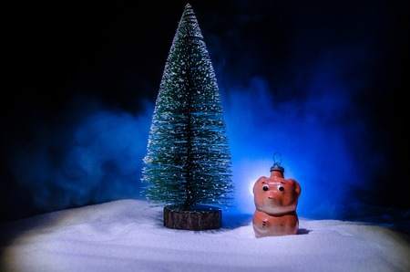 Toy dog - a symbol of the new year under the snow against the background of fir branches. Stock Photo