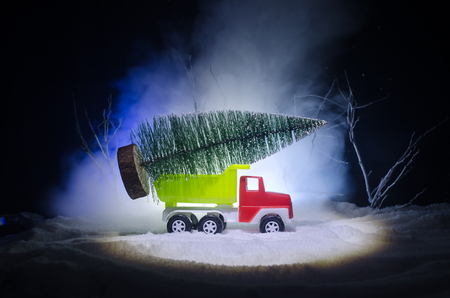 New year holiday concept. Miniature car with fir tree on Snowy Winter Fores, or toy car carrying a christmas tree and at night time. foggy background Stock Photo