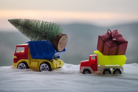 New Year holiday concept. Miniature car with fir tree on Snowy Winter Forest, or toy car carrying a Christmas tree and at snowy road. Nature blurred background. Selective focus Stock Photo