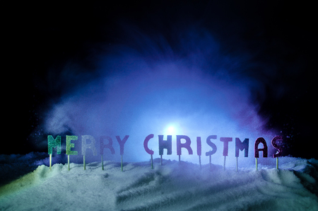 Words Merry christmas on a snow field, with dark background with chrismas tree. New year concept. Empty space. Useful as greeting card
