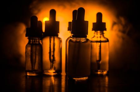 vape 개념입니다. 어두운 배경에 구름과 vape 액체 병을 연기. 조명 효과. 배경 또는 vape 광고 또는 vape 배경으로 유용합니다. 스톡 콘텐츠