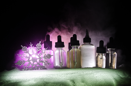 Electronic cigarette with vape liquids and christmas decorations on bokeh lights background with New Year atributes or symbols. Selective focus Banco de Imagens