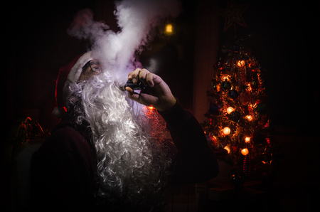 Santa Clause vaping electronic cigarette dressed as traditional Santa on a dark toned background with vape clouds. Selective focus. Fir tree at backside