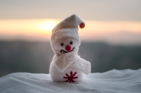 New Year Christmas concept. The snowman stands on snow with blurred nature background. White snowman surrounded by Christmas trees on evening background. Toy Decoration. Selective focus. Empty space