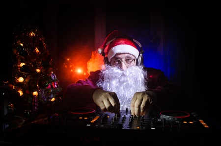 DJ Santa Claus mixing up some Christmas cheer. Dark disco club toned background. New Year's Eve event in the rays of light. Useful as poster or greeting card. Selective focus