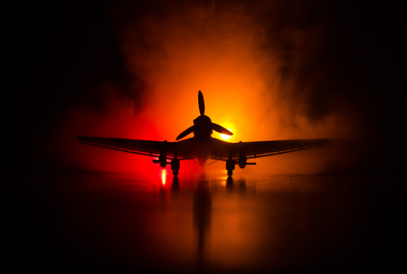 jet-propelled model plane in possession. Dark orange fire background. War scene. Selective focus