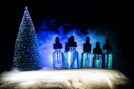 Electronic cigarette with vape liquids and christmas decorations on bokeh lights background with New Year atributes or symbols. Selective focus Stock Photo