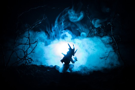 Silhouette of fire breathing dragon with big wings on a dark blue cold background. Horror image 스톡 콘텐츠