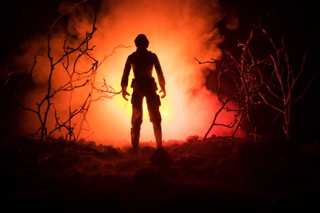 Military soldier silhouette with gun. War Concept. Military silhouettes fighting scene on war fog sky background, World War Soldier Silhouette Below Cloudy Skyline At night. Attack scene