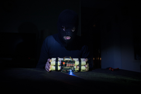 Terrorist making timebomb. terrorism and dangerous concept. Dark background