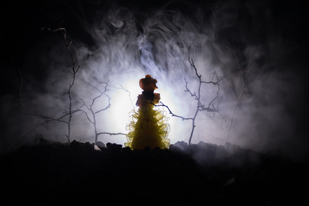 Alone girl with the light in the forest at night, or toned foggy night at forest. Horror Halloween concept. Selective focus