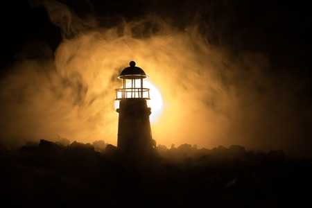 Lighthouse with light beam at night with fog. Selective focus