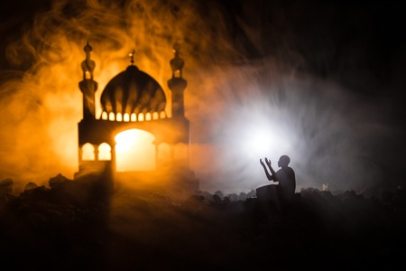 Silhouette of mosque building on toned foggy background. Ramadan Kareem background. Mosque at sunset. Praying people