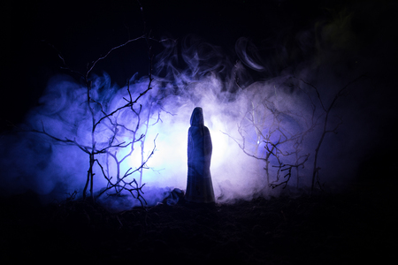 Alone girl with the light in the forest at night, or blue toned night forest at the fog time