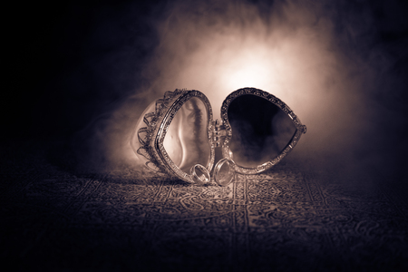 Opened old vintage silver heart-shaped casket for wedding rings on dark toned smoky light background. Valentine love concept. Selective focus