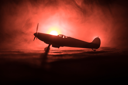 British jet-propelled model plane in possession. Dark orange fire background. War scene. Selective focus