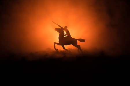 World war officer (or warrior) rider on horse with a sword ready to fight and soldiers on a dark foggy toned background. Stock Photo