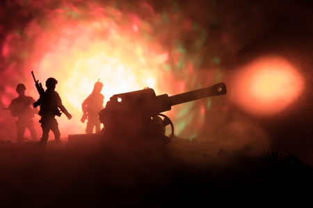Battle scene with arillery and standing soldiers. Silhouette of old field gun standing at field ready to fire. Stock Photo