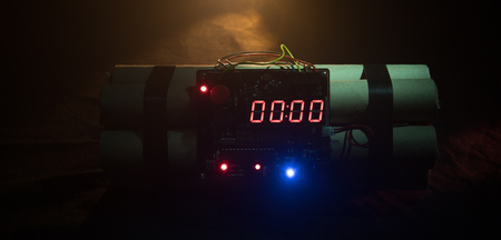 Image of a time bomb against dark background. Timer counting down to detonation illuminated in a shaft light shining through the darkness, conceptual image Foto de archivo