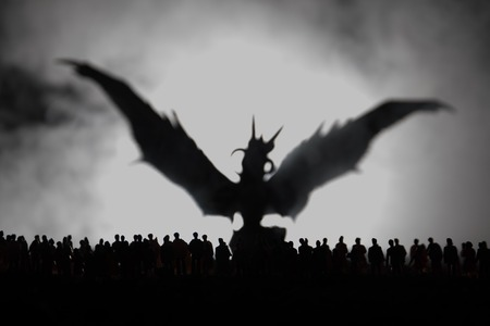 Blurred silhouette of giant monster prepare attack crowd during night. Selective focus. Stock Photo