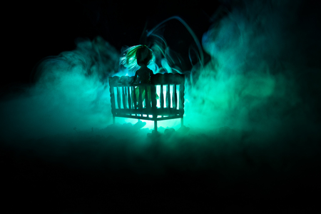 Old creepy eerie wooden baby crib in dark toned foggy background. Horror concept. Scary baby and bed silhouette in dark. Halloween decoration shot. Selective focus