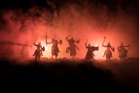 Scène de bataille médiévale avec cavalerie et infanterie. Silhouettes de figures en tant qu'objets séparés, combattez les guerriers sur un fond brumeux aux tons sombres. Scène de nuit. Mise au point sélective Banque d'images