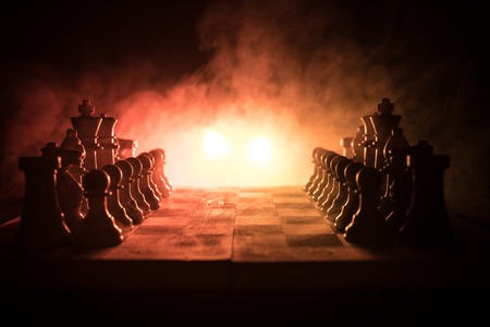 Chess board game concept of business ideas and competition and strategy ideas concep. Chess figures on a dark background with smoke and fog. Business leadership and confidence concept. Selective focus