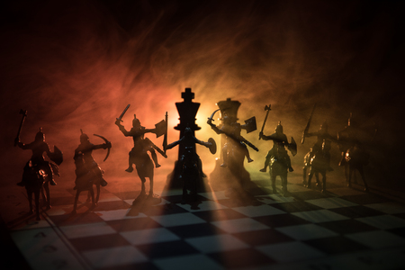 Medieval battle scene with cavalry and infantry on chessboard. Chess board game concept of business ideas and competition and strategy ideas Chess figures on a dark background with smoke and fog. Stok Fotoğraf