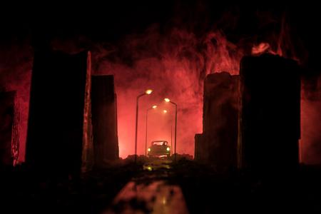 Rue vide de la ville incendiée, flammes au sol et explosions de fumée au loin. Vue apocalyptique du centre-ville comme concept d'affiche de film de catastrophe. Scène de nuit. Ville détruite par la guerre.