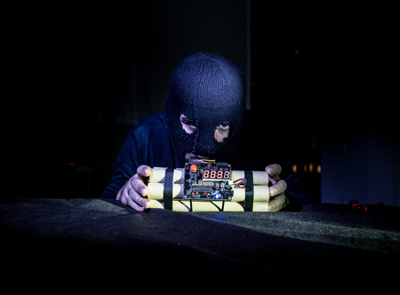 Terrorist making timebomb. terrorism and dangerous concept. Dark background