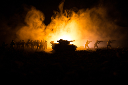 War Concept. Military silhouettes fighting scene on war fog sky background, World War Soldiers Silhouettes Below Cloudy Skyline At night. Attack scene. Armored vehicles. Tanks battle. Decoration Stock Photo
