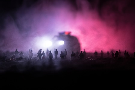 Silhouettes of a crowd standing at field behind the blurred foggy background. Selective focus. Revolution, people protest against government, man fighting for rights Stock Photo