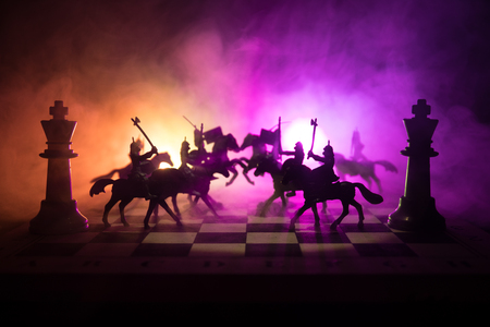 Medieval battle scene with cavalry and infantry on chessboard. Chess board game concept of business ideas and competition and strategy ideas Chess figures on a dark background with smoke and fog. Stock Photo