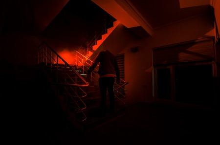 Ghost in Haunted House at stairs, Mysterious silhouette of ghost man with light at stairs, Horror scene of scary ghost spooky llights . Scary hall. Halloween background.