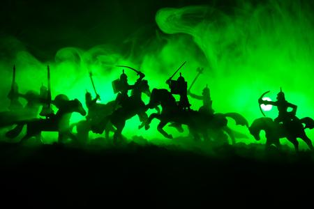 Mittelalterliche Kampfszene mit Kavallerie und Infanterie. Silhouetten von Figuren als separate Objekte, Kampf zwischen Kriegern auf dunkel getönten nebligen Hintergrund. Nachtszene. Tiefenschärfe